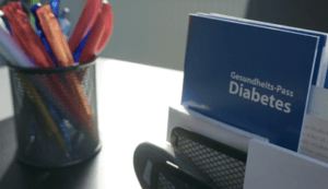 Schreibtisch mit Stiften und Infoflyern Diabetes